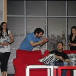 Theatre performance of the shy actor. Two men, two women, one red couch. One man yells at the other man