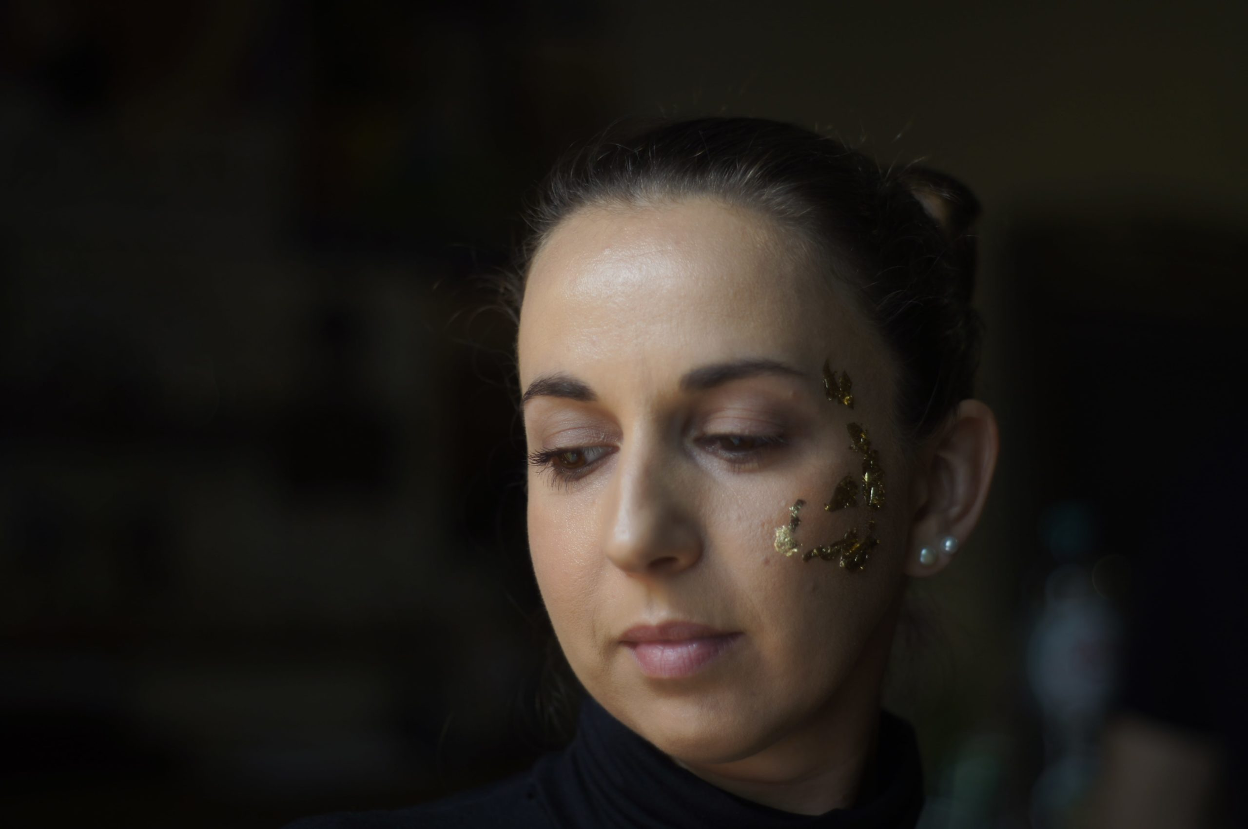closeup on a woman with dark brown hair and brown eyes, looking down. Golden flakes cover her left cheek and temple
