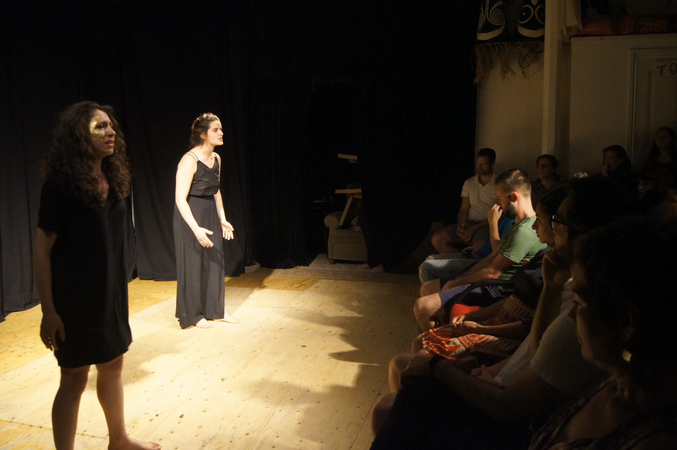 Theatre performance, two women on stage with black dresses, standing in front of audience. They are crying while speaking.