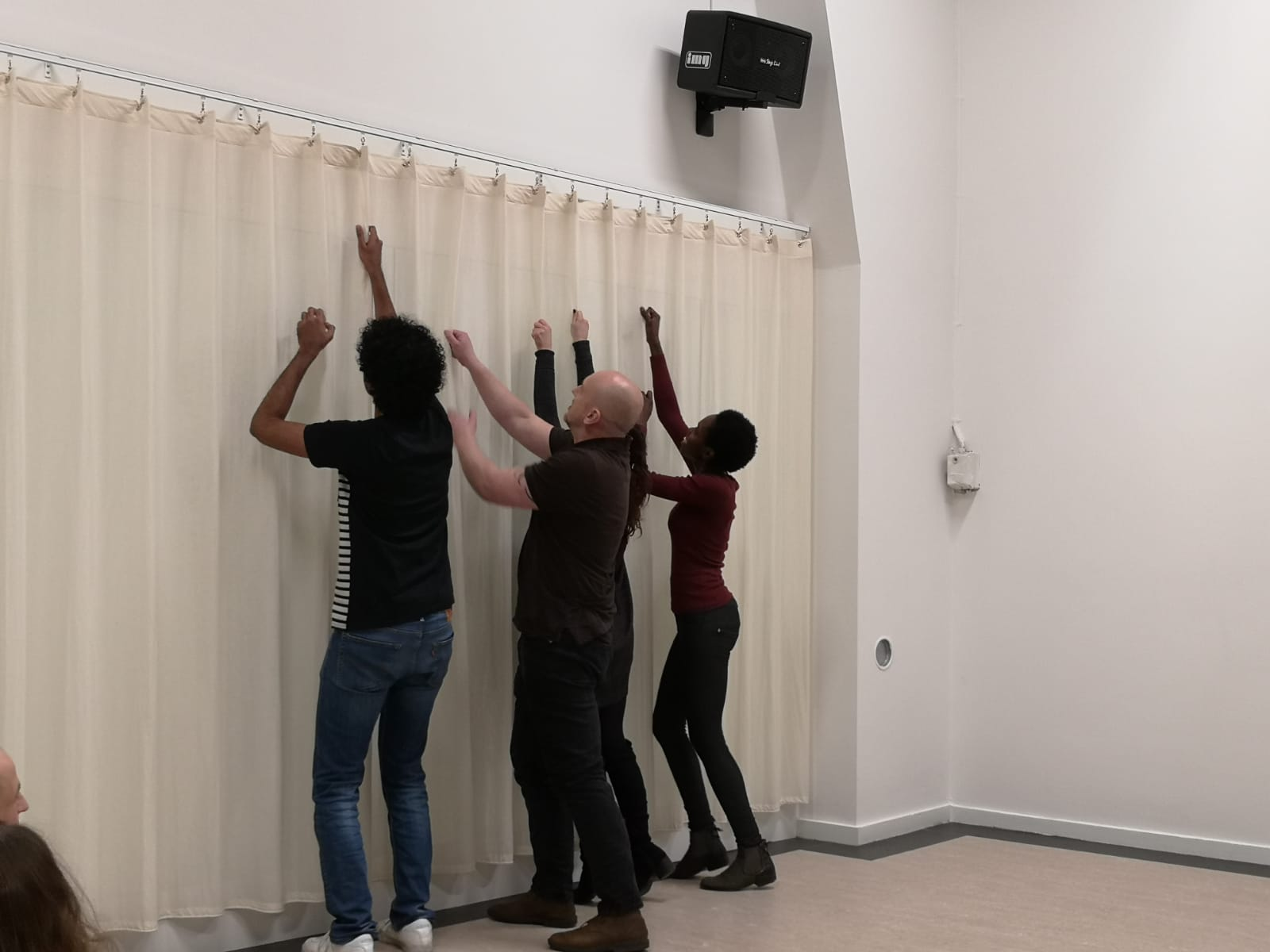 Acting Class Act Attack. A group of four people stand in a row, facing a curtain. Their arms reach up, like they want to bring down the curtain.
