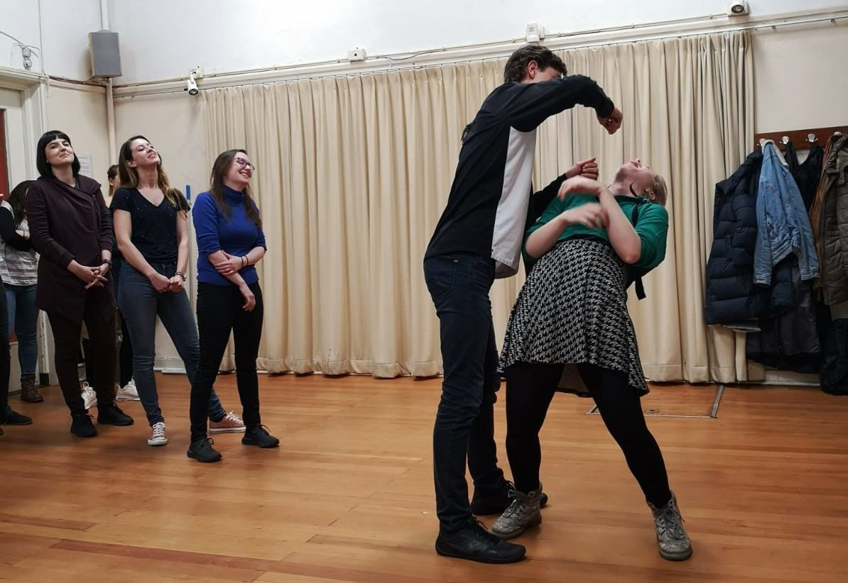 Improv Class Act Attack. A person has their arm hanging on top of another person's face, like trying to feed or punch them. The second person, clearly a girl, leans backwards