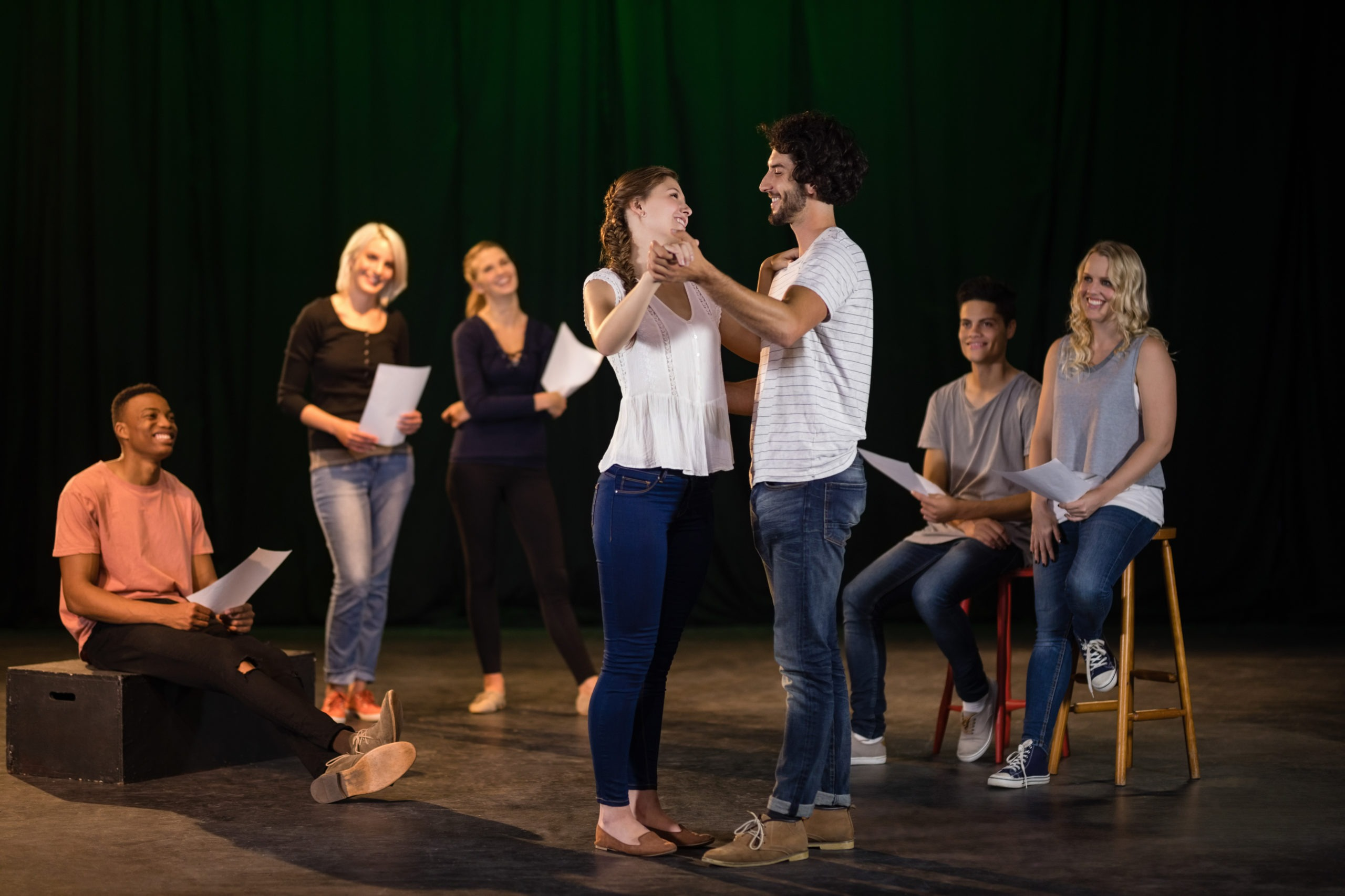 Actors practicing a play on stage. Five people form a semi-circle around a couple (man and woman) who look each other in the eye and are ready to dance waltz