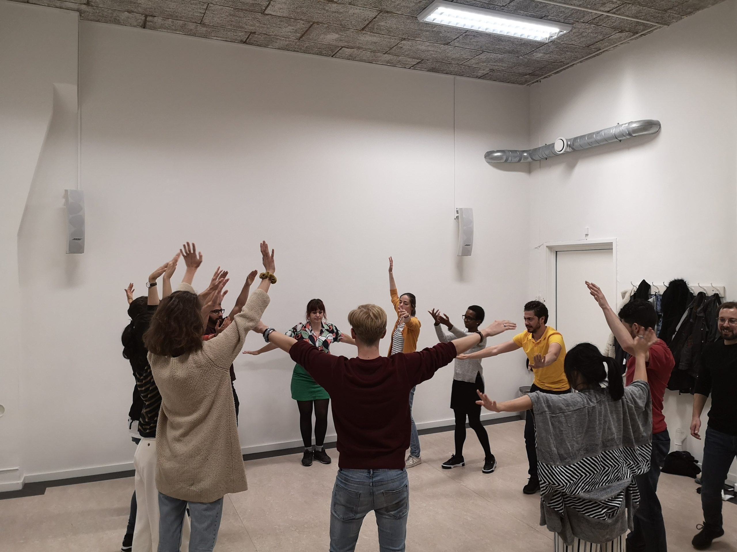 Pure improv for beginners. A group of people form a semi-circle holding their hands up in the air. Some hold their arms sideways.