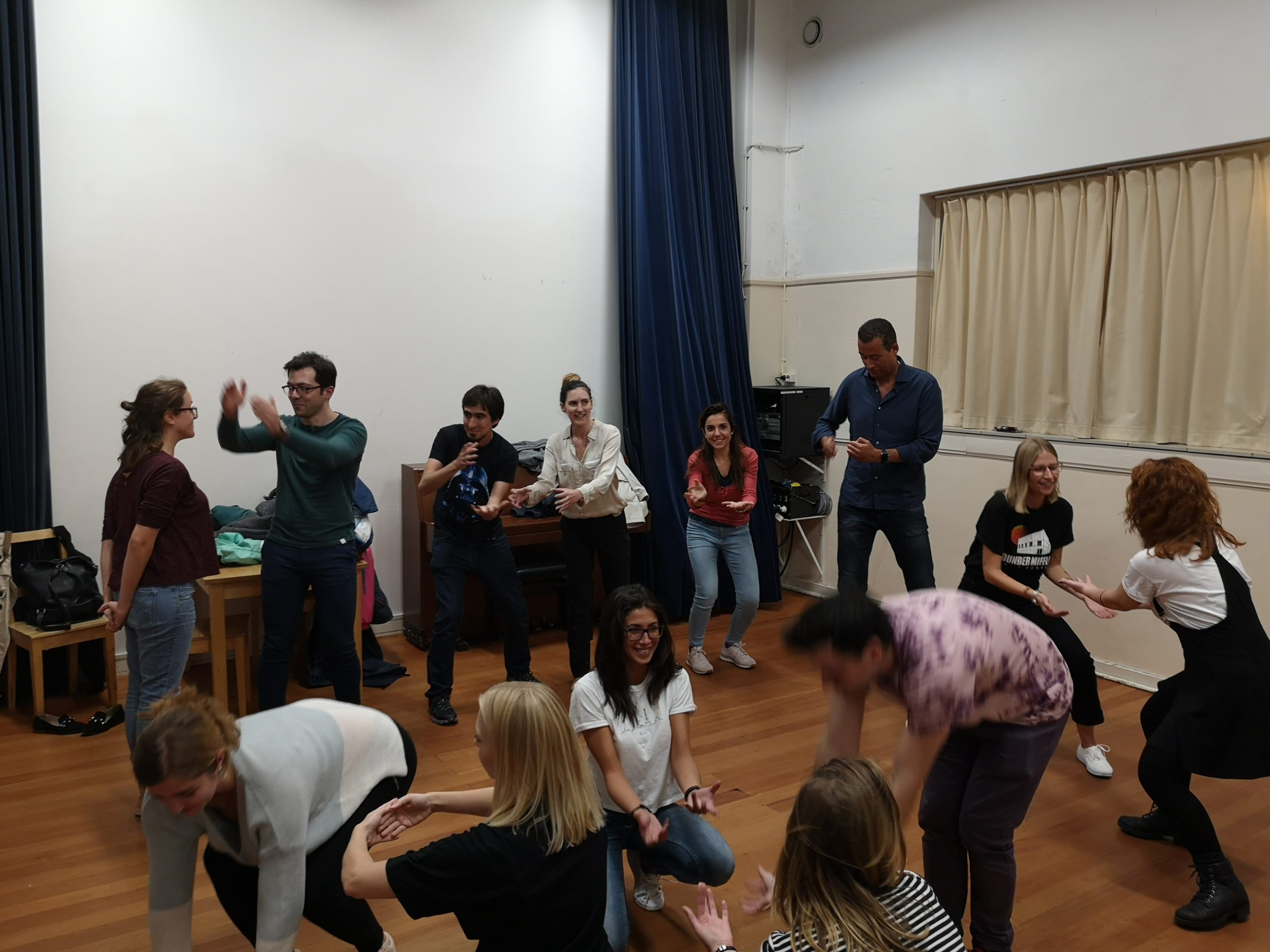 From the improv and physical class. A group of people do an exercise. Some are sitting, some kneeling, some standing, everybody is moving their arms differently.
