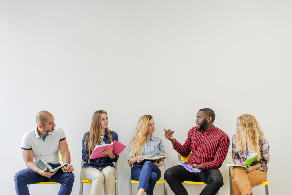 five people sitting on yellow chairs with their backs against a white wall. One man speaks and the others look at him
