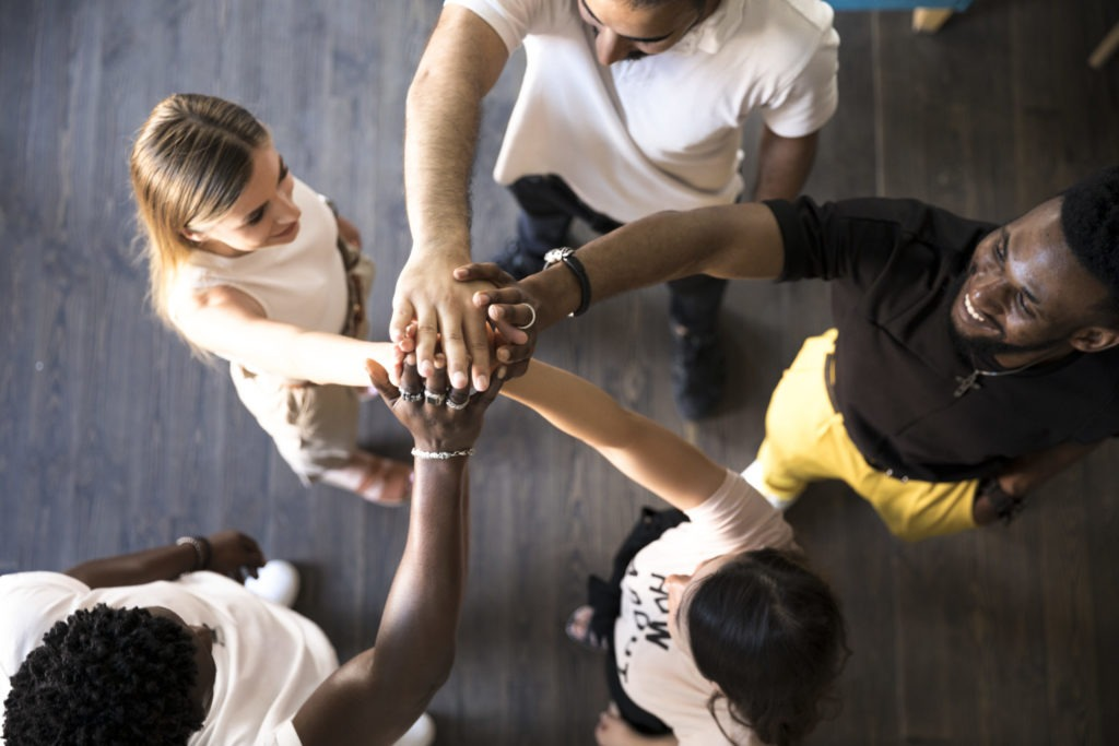five people standing in a circle reaching their right arms in the middle so that their hands touch. They smile. View from above.