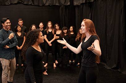 Acting courses. A group of people (dressed in black) are watching a red-haired girl and a dark-haired girl talk, doing hand gestures