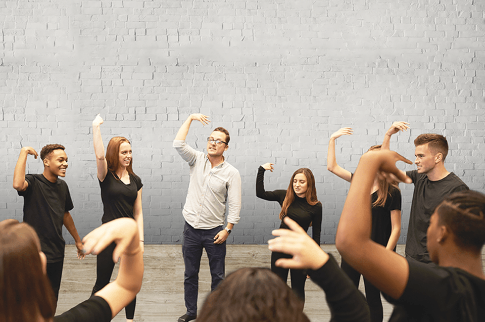 Team building business workshop. A group of people wearing black, except for one man with glasses wearing a white shirt, have their arms lifted in a 90 degree angle with their wrist also in a 90 degree angle. Background: Grey brick wall