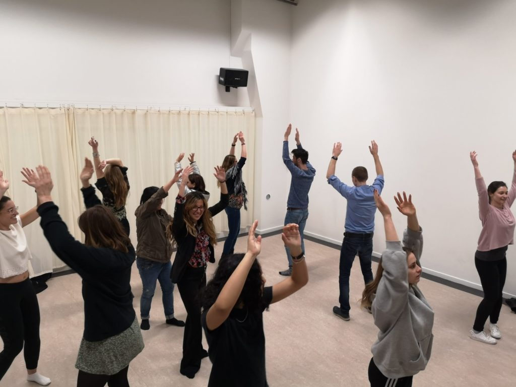 Photo from a class. A group of people are scattered around the room, with their hands in the air