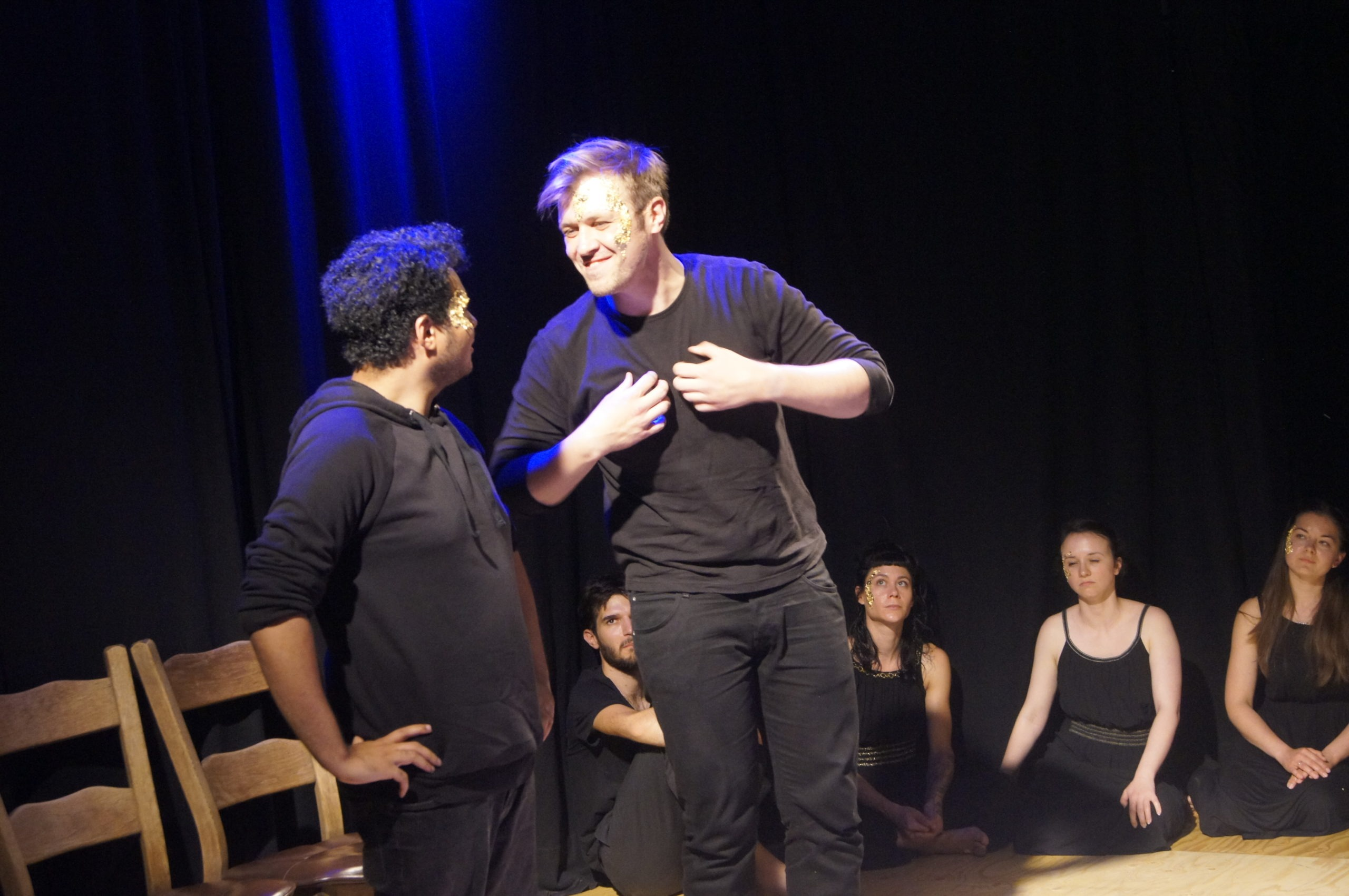 Photo from the theatre performance Keeping up with the Greeks. Two male actors on stage, standing, wearing black clothes, talking, one of them grins and holds his chest with his hands. Behind them, four actors on the floor, black clothes, golden flakes on their face