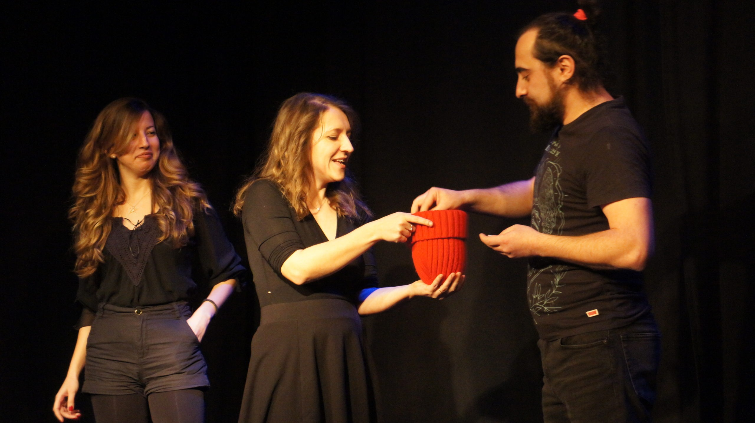 Act Attack's improv and physical show. Two women and a man on stage wearing black. The woman in the middle gives the man a red beanie to draw something out of