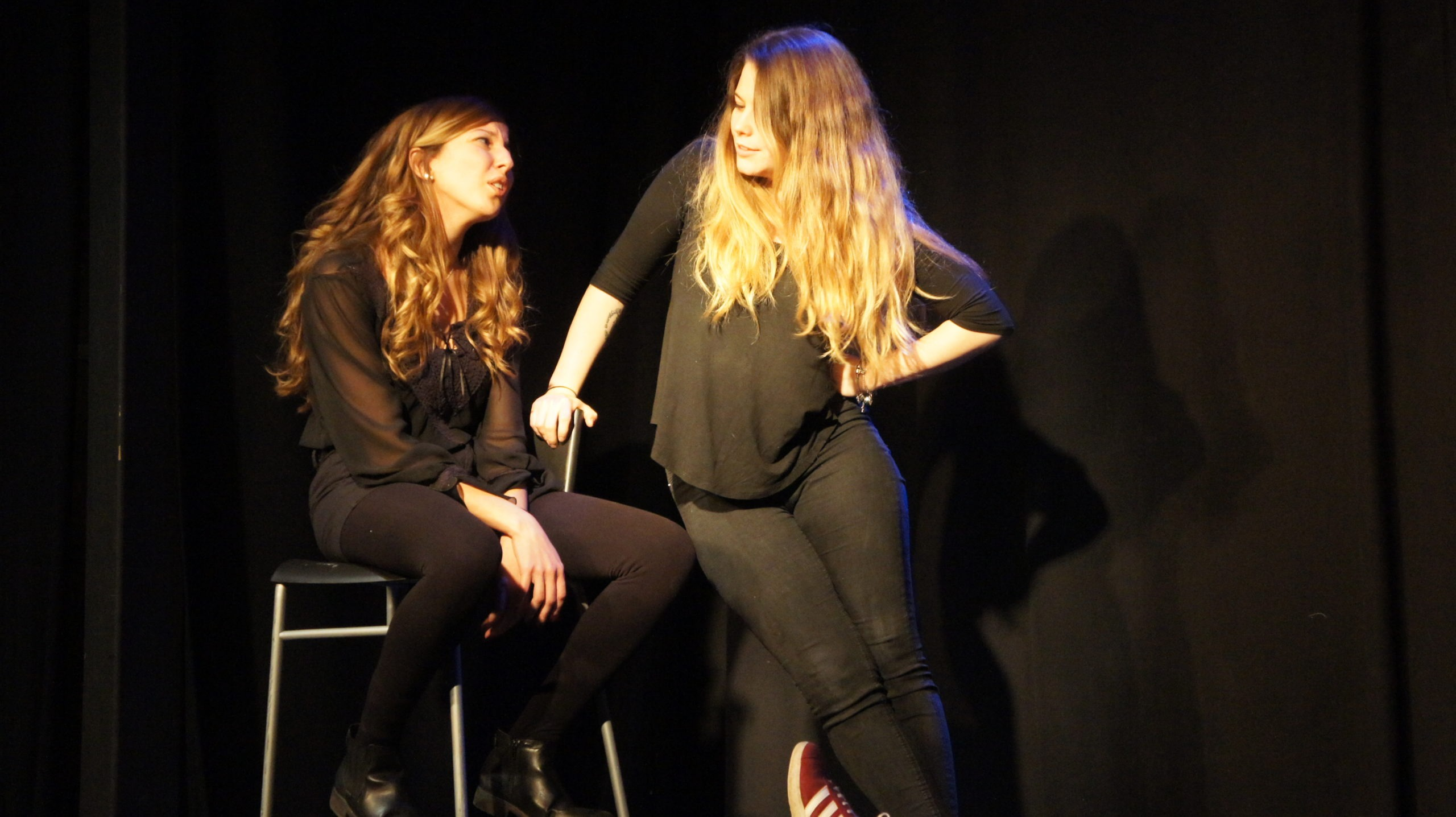 Act Attack's improv and physical show. Two girls on stage, wearing black. One sitting on a bar stool, the other leaning on her. They're talking