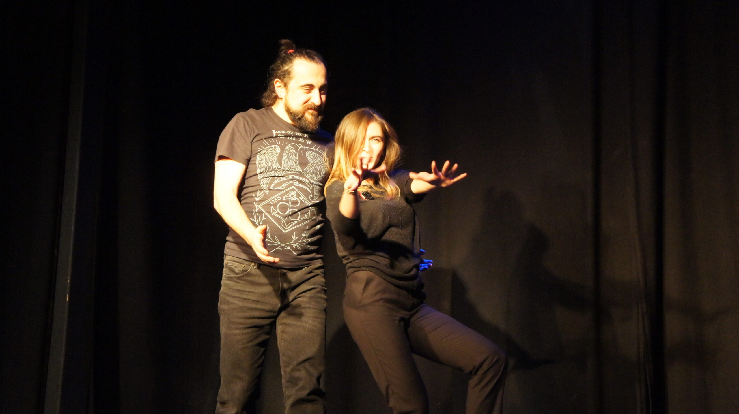 Act Attack's improv and physical show. A man and a woman on stage wearing black. The woman is posing or reaching her arms to show something, the man looks at her grinning