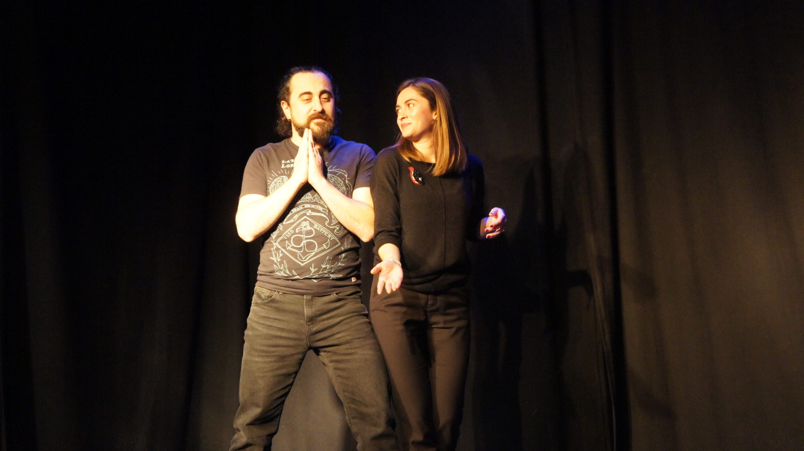 Act Attack's improv and physical show. A man and a woman on stage wearing black. The woman looks at the man showing him something on the floor, he has his hands placed in front of his heart, like praying