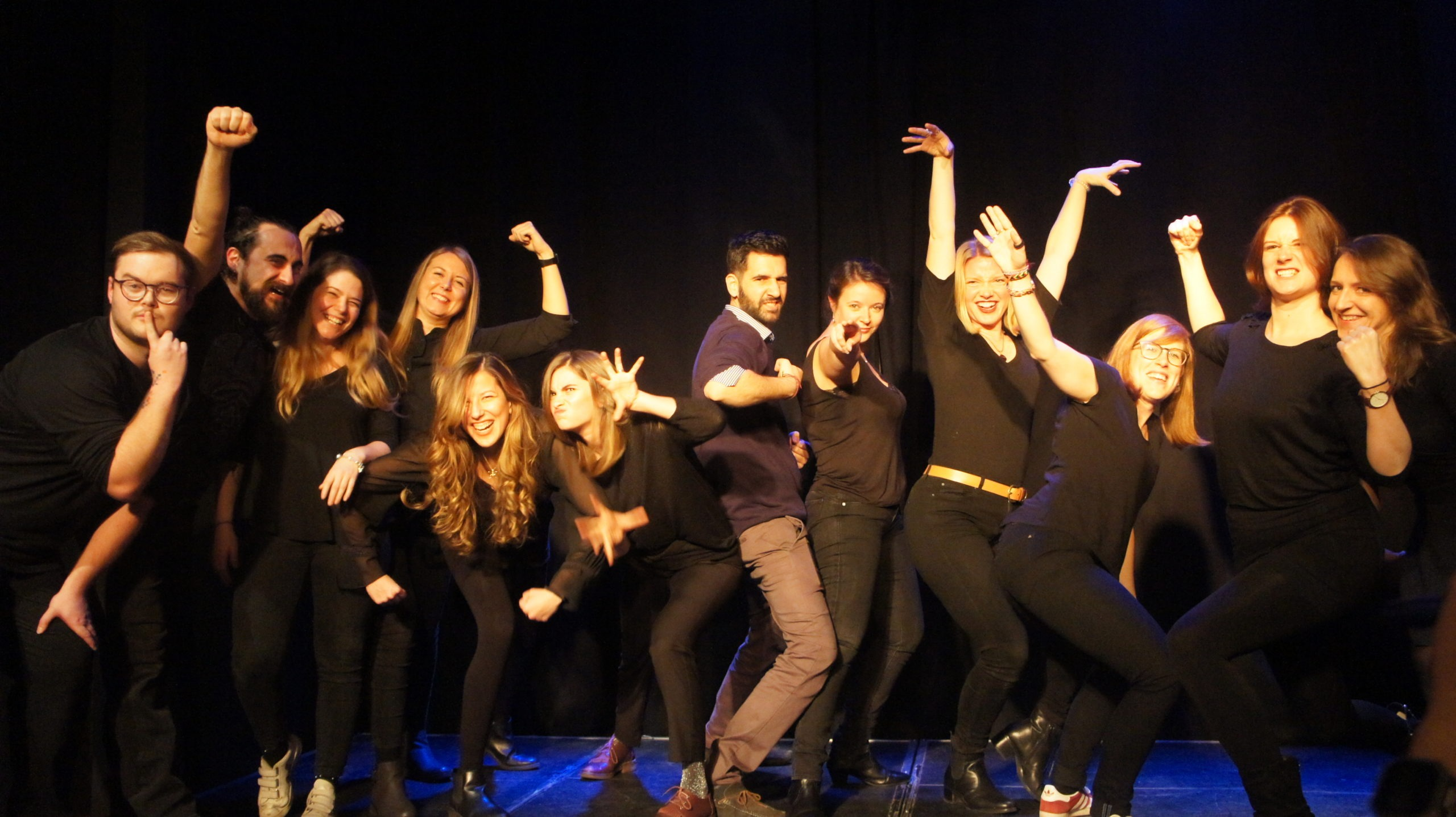Act Attack's improv and physical show. A group of people on stage wearing black clothes. Group photo after the show, everybody picks a different pose