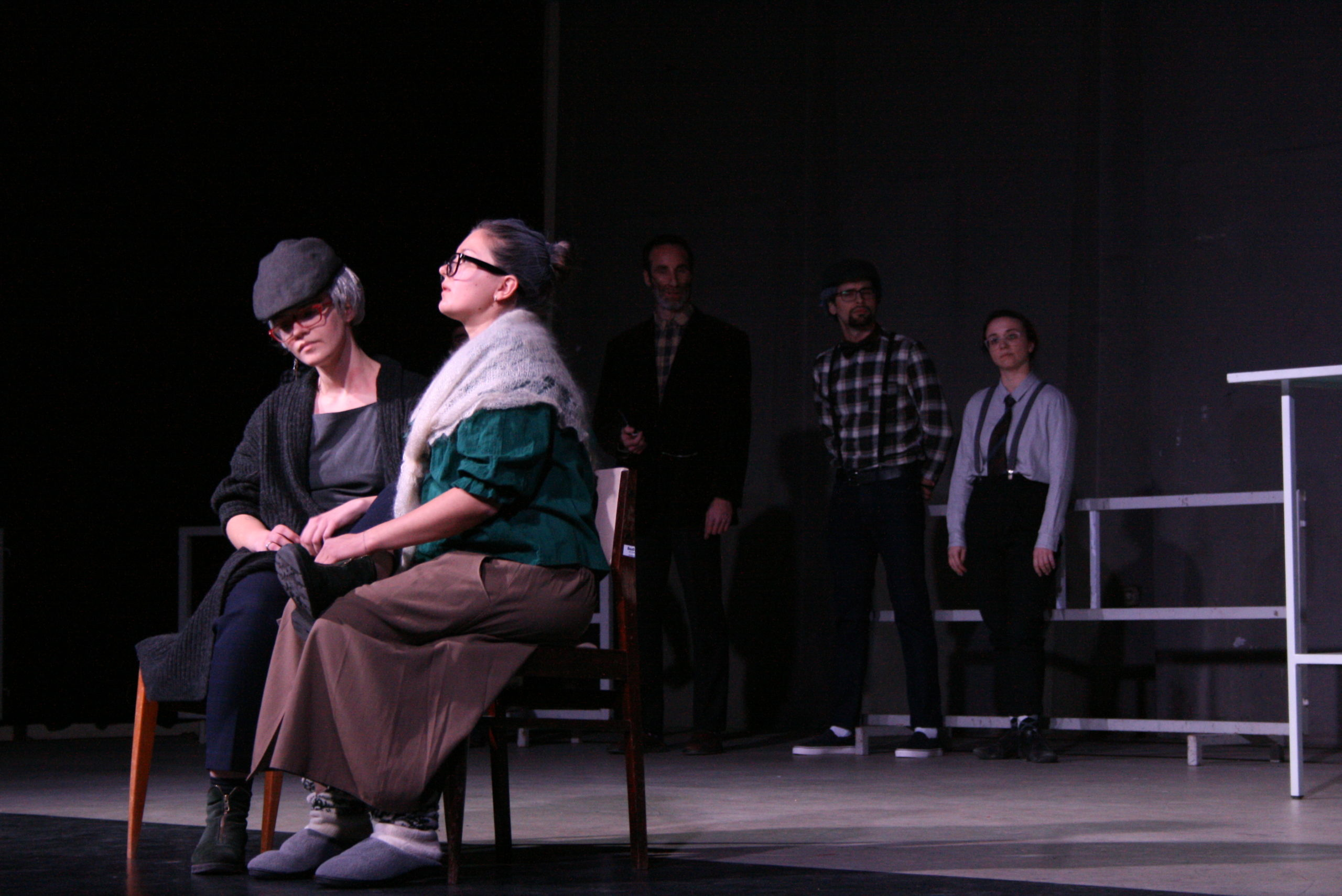 """Photo from the show """"The Chairs"""". Three actors stand at the back of the stage, wearing old-fashioned clothes, like blue plaid shirts and caps. Two female actors sit on chairs at the front, dressed like old ladies"""