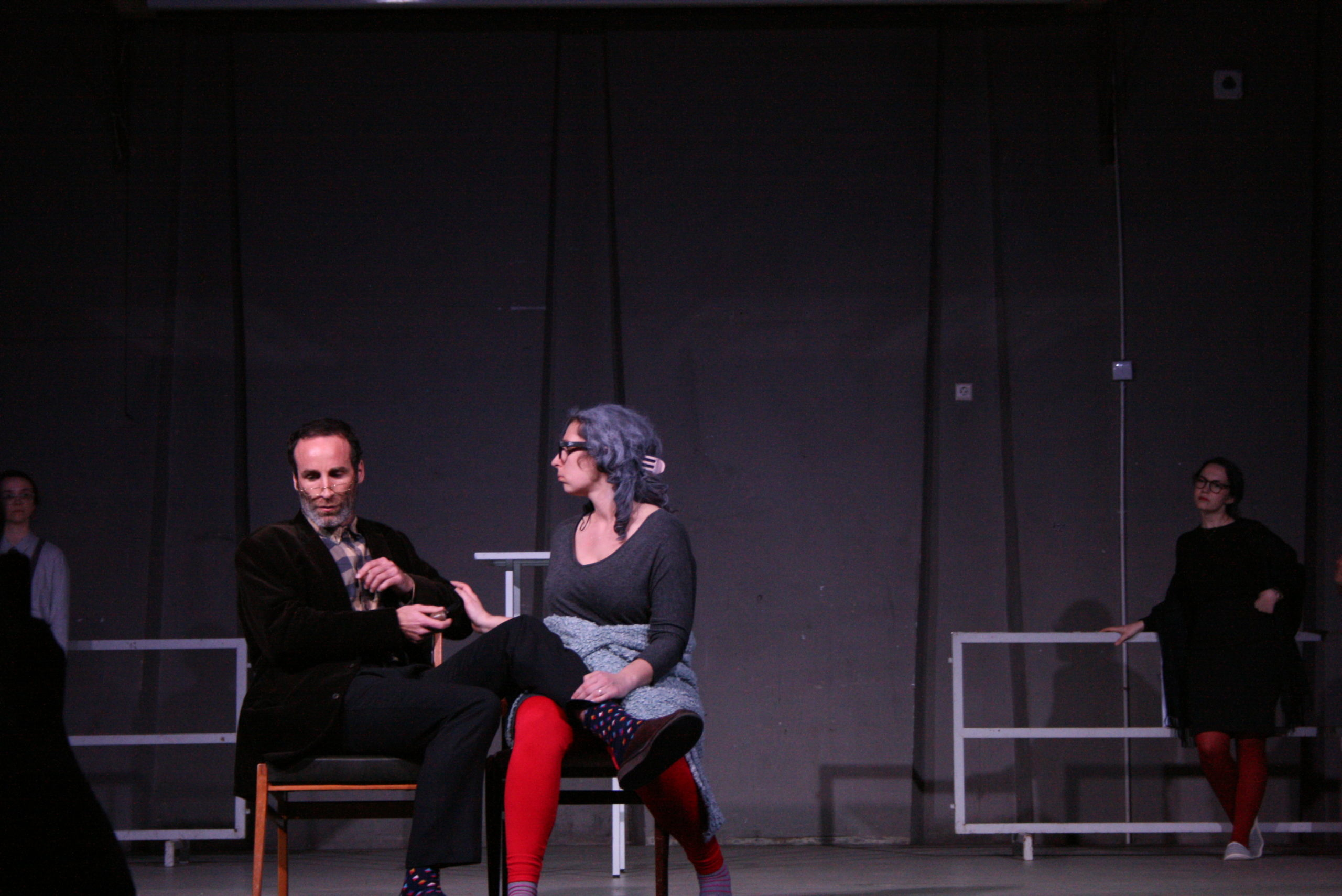 """Photo from the show """"The Chairs"""". A male and a female actor sit on chairs. He has his right leg laid on her lap and she is touching his arm"""