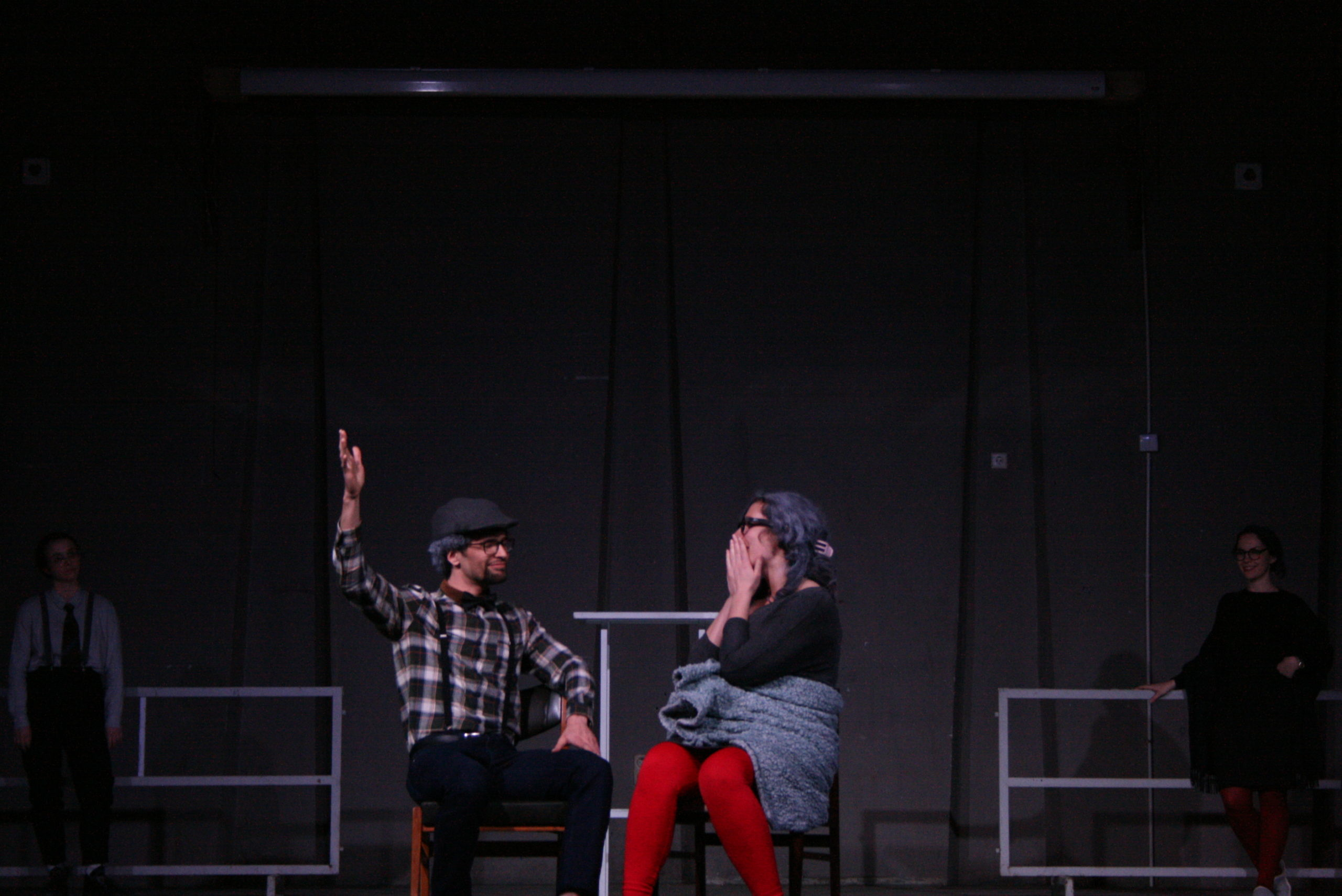 """Photo from the show """"The Chairs"""". A male and a female actor sit on chairs. He has is right arm up and she is touching her face in shock"""