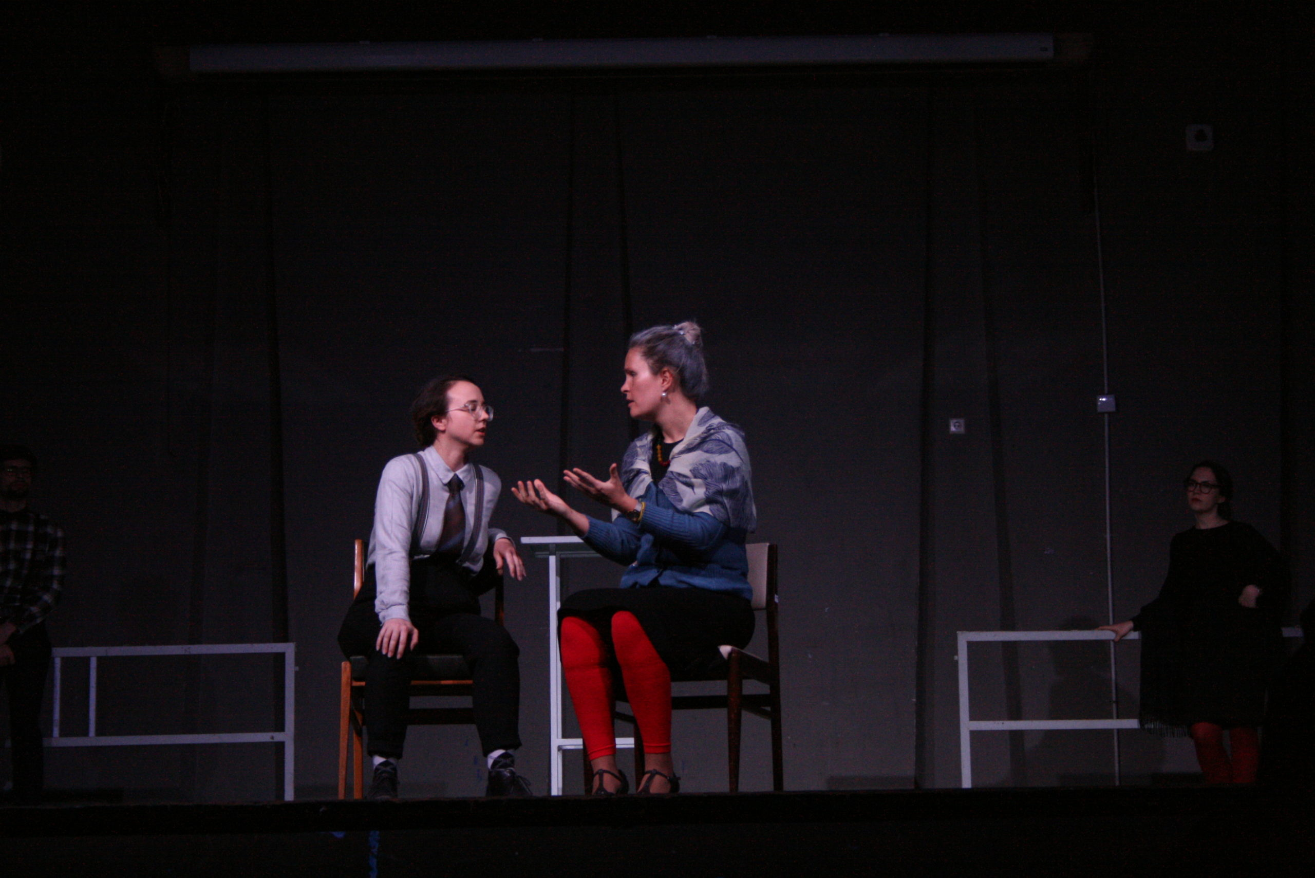 """Photo from the show """"The Chairs"""". Two female actors sit on chairs, talking, one of them dressed as male."""