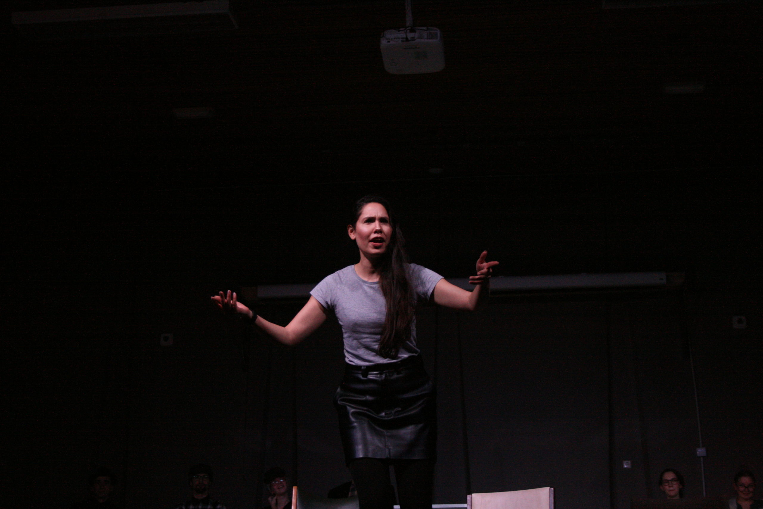 """Photo from the show """"The Chairs"""". A female actor addresses the audience. She looks angry, reaching out both her arms in question"""