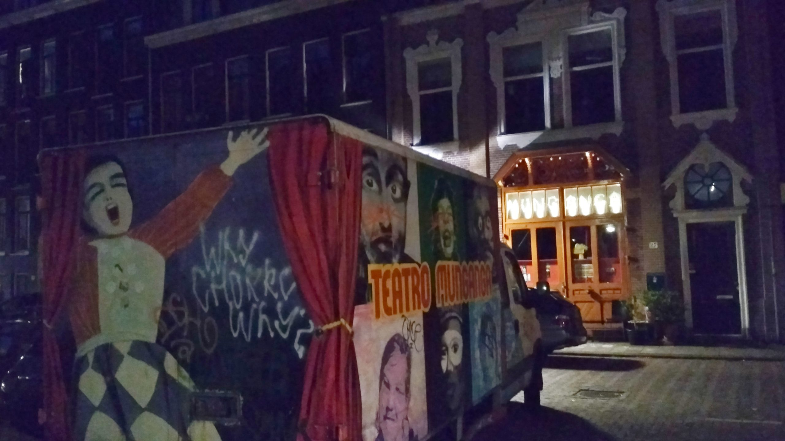 """A truck with the logo """"teatro munganga"""" and images of 1900s theatre, parked outside of an Amsterdam house."""
