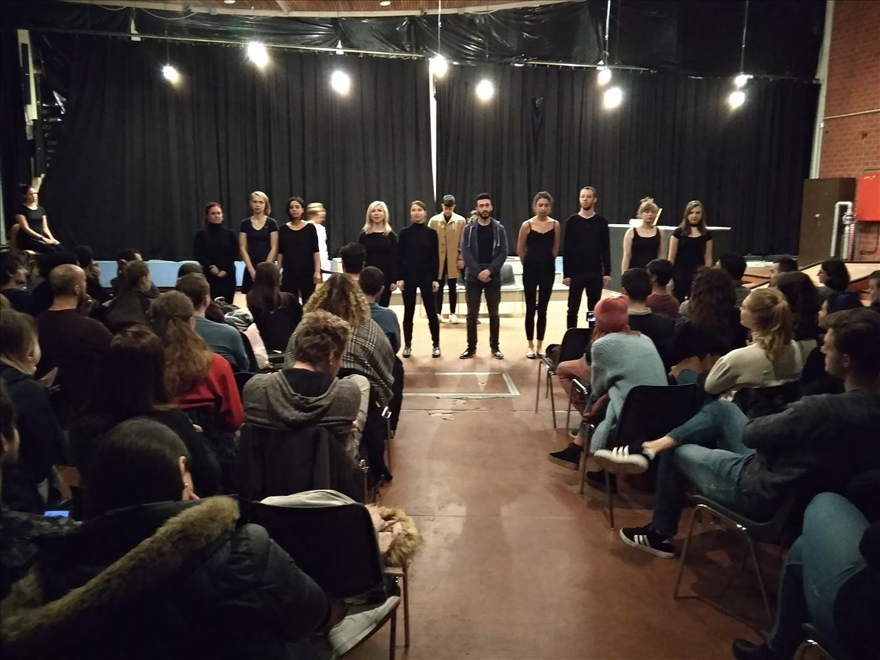 """Photo from the show """"Skin of our Teeth"""". The cast of eleven people stand on stage in front of the audience"""