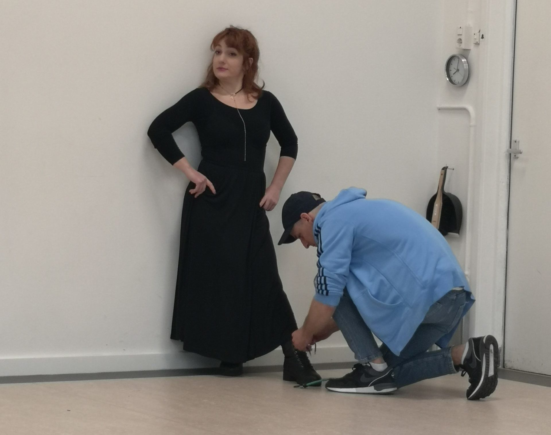 Acting Class Act Attack. Red-haired girl with black dress, her back against the wall, her arms on her waist. A man with a light blue jacket is kneeled infront of her, tying her shoe.
