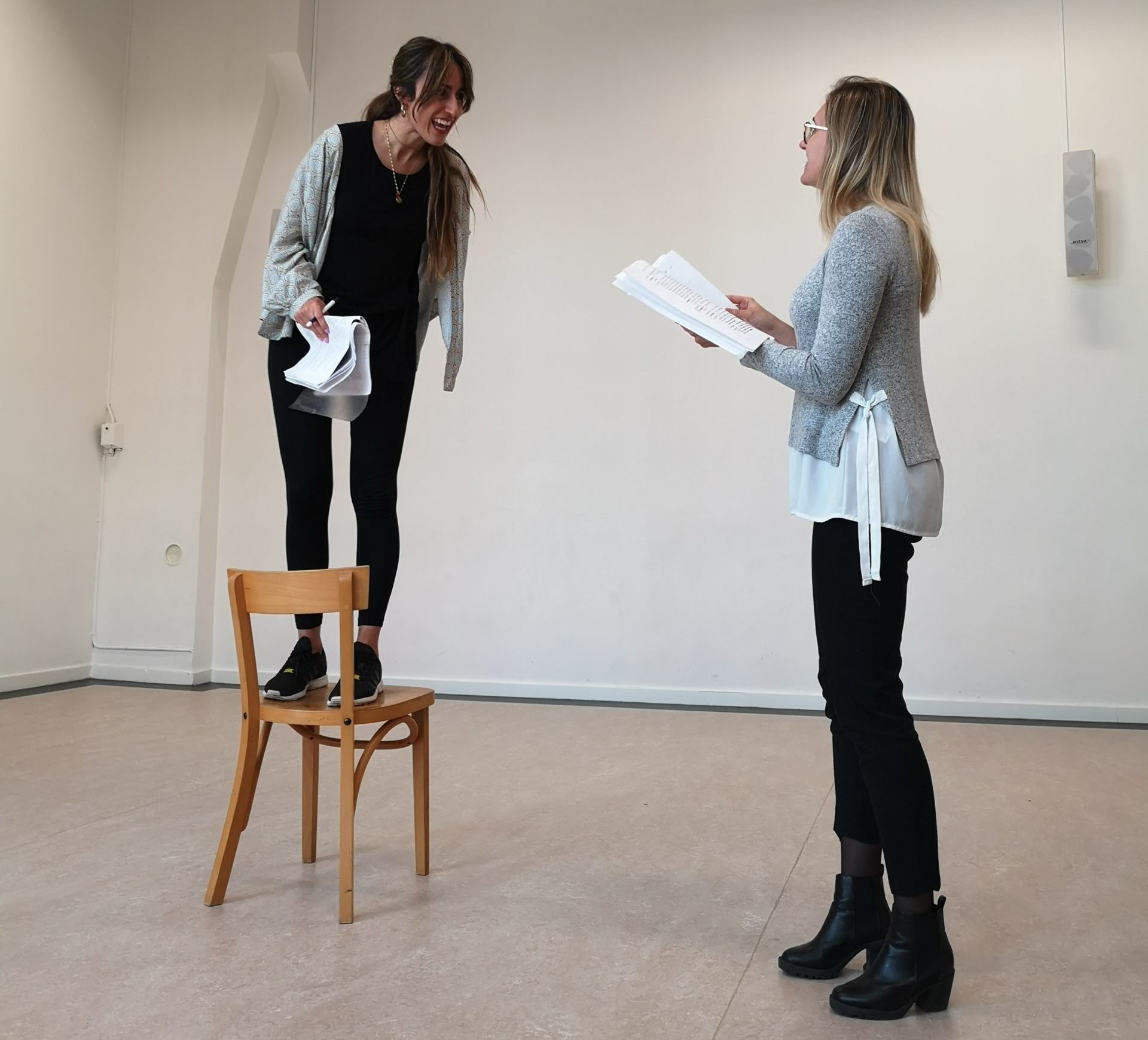 Acting Class Act Attack. Two women read lines, one is standing on the chair, laughing or screaming, the other one is standing up.
