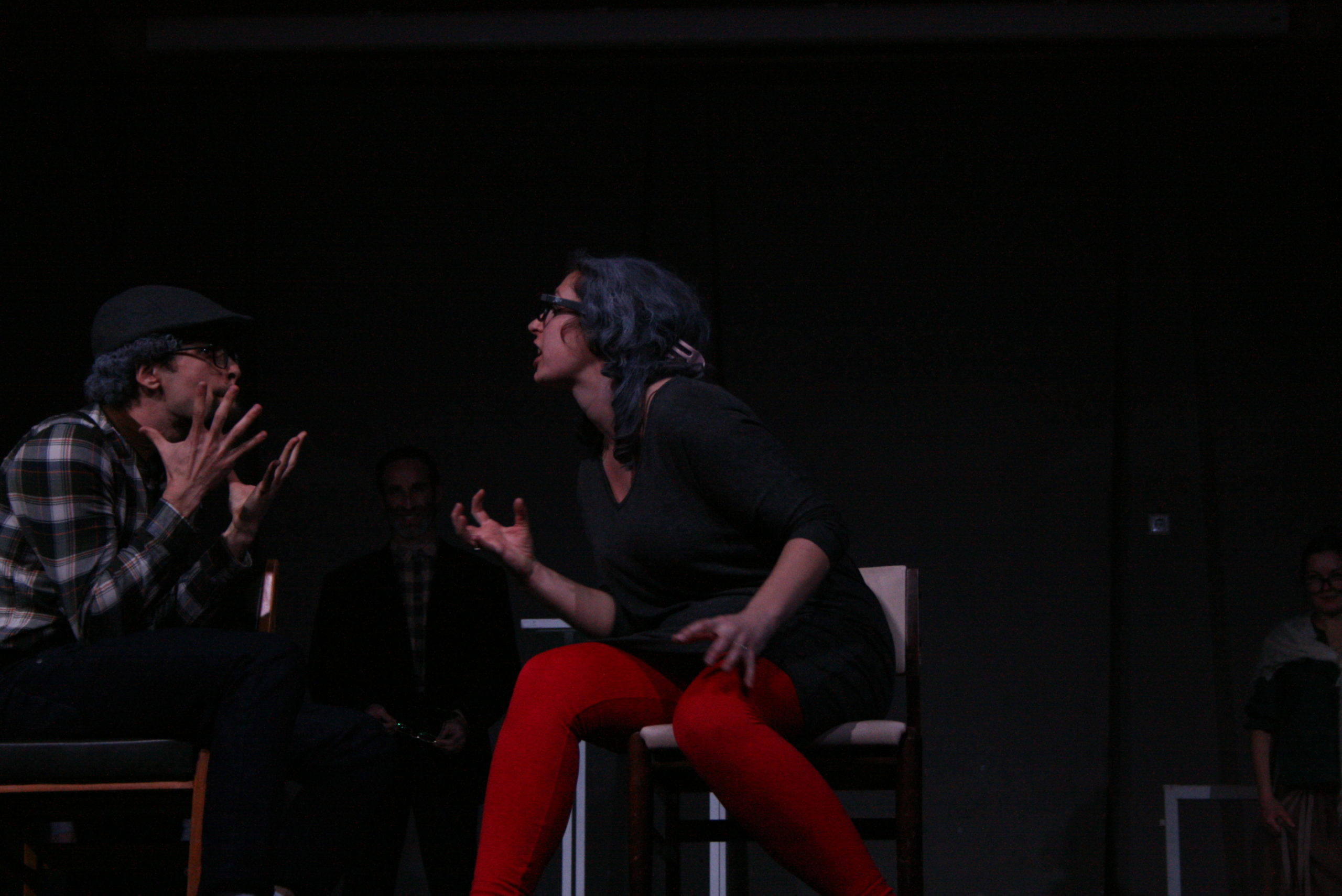"""Photo from the show """"The Chairs"""". A male and a female actor sit on chairs, arguing. They are dressed in old-fashioned clothes"""