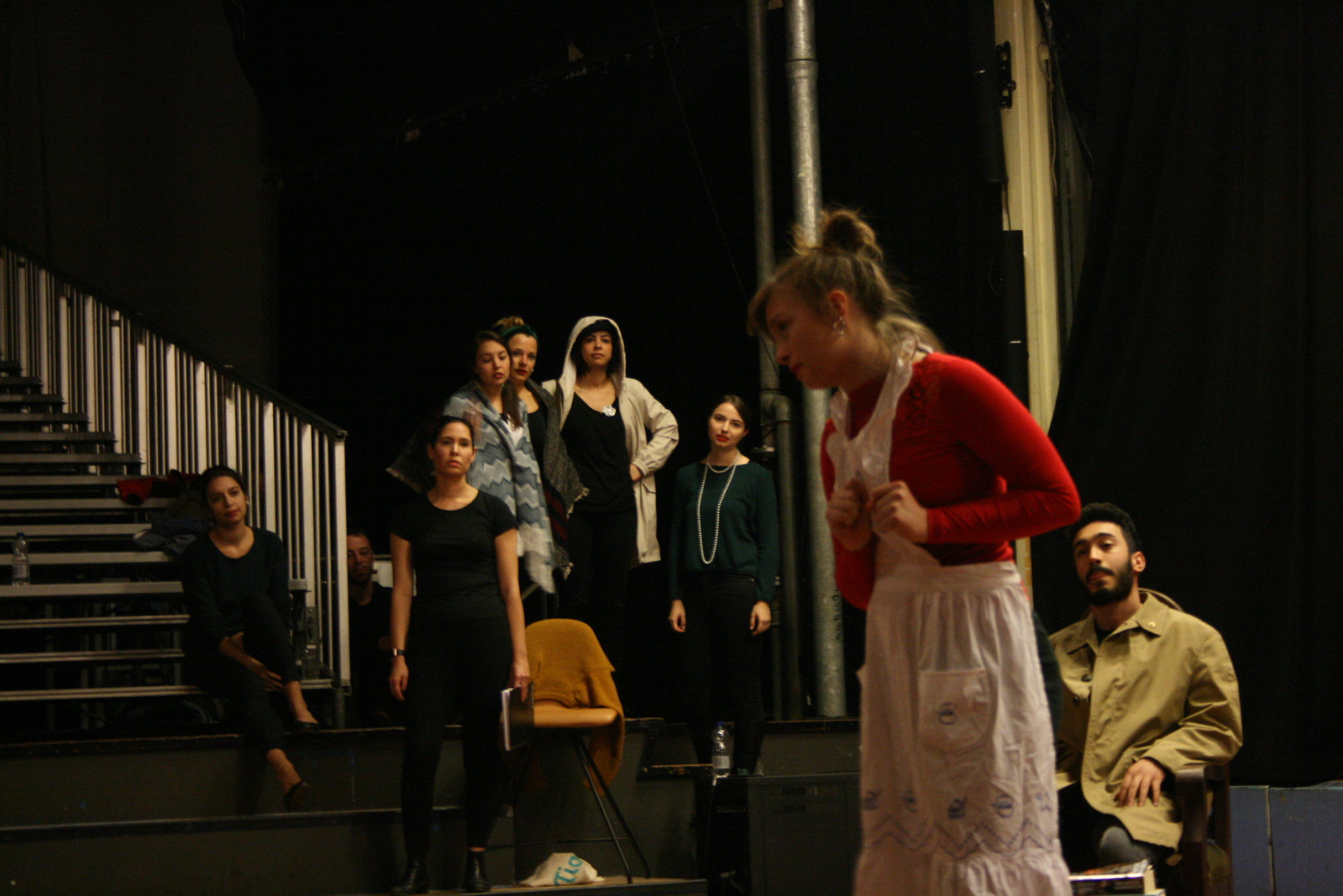 """Photo from the show """"Skin of our Teeth"""". A female actor dressed like a maid on stage, her hands clenched in fists and on her chest. Behind her is the rest of the cast, looking at her"""
