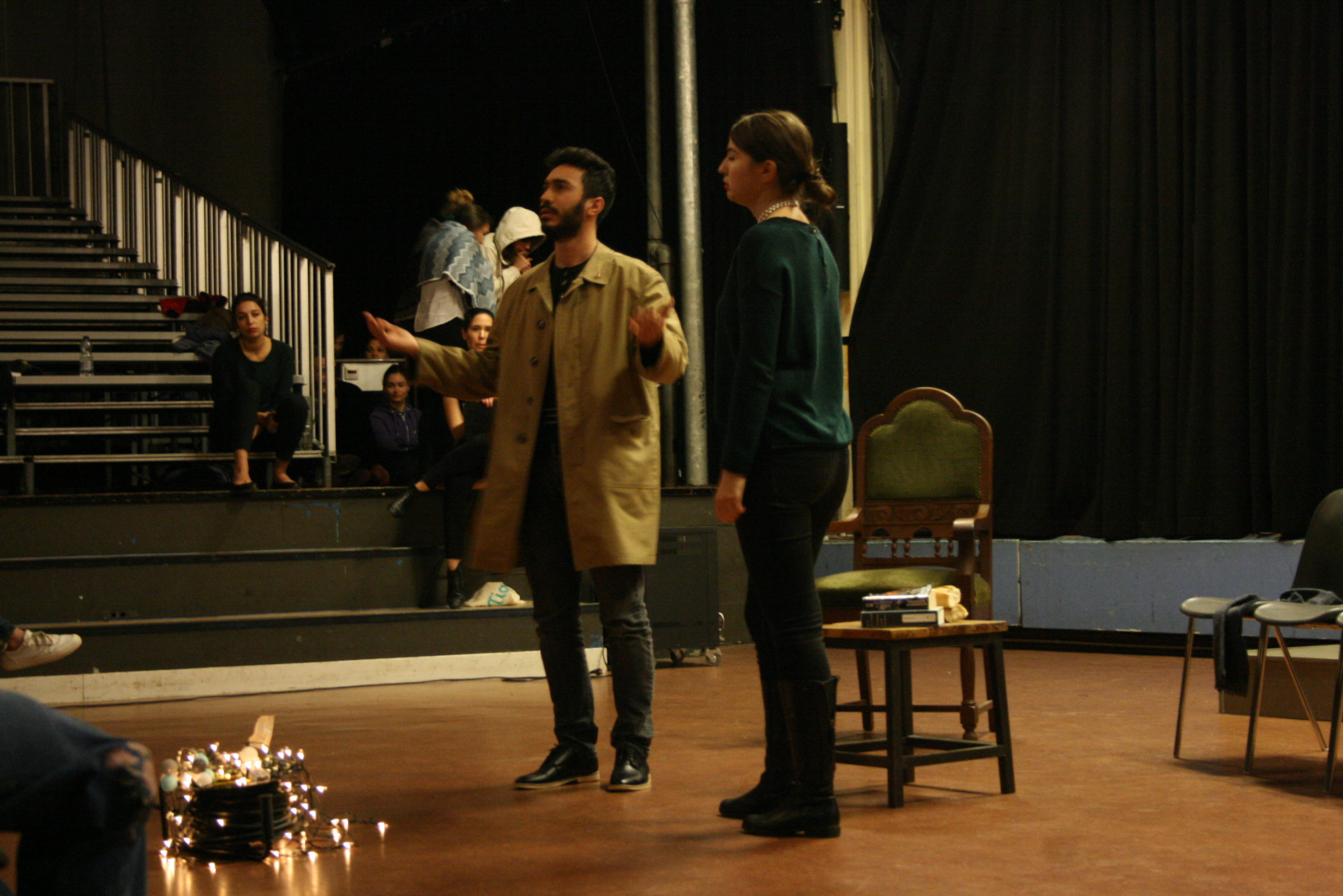 """Photo from the show """"Skin of our Teeth"""". Two actors are on stage, one dressed like a 1920s madame and a man wearing a beige half-long coat. He lifts is arms in wonder"""