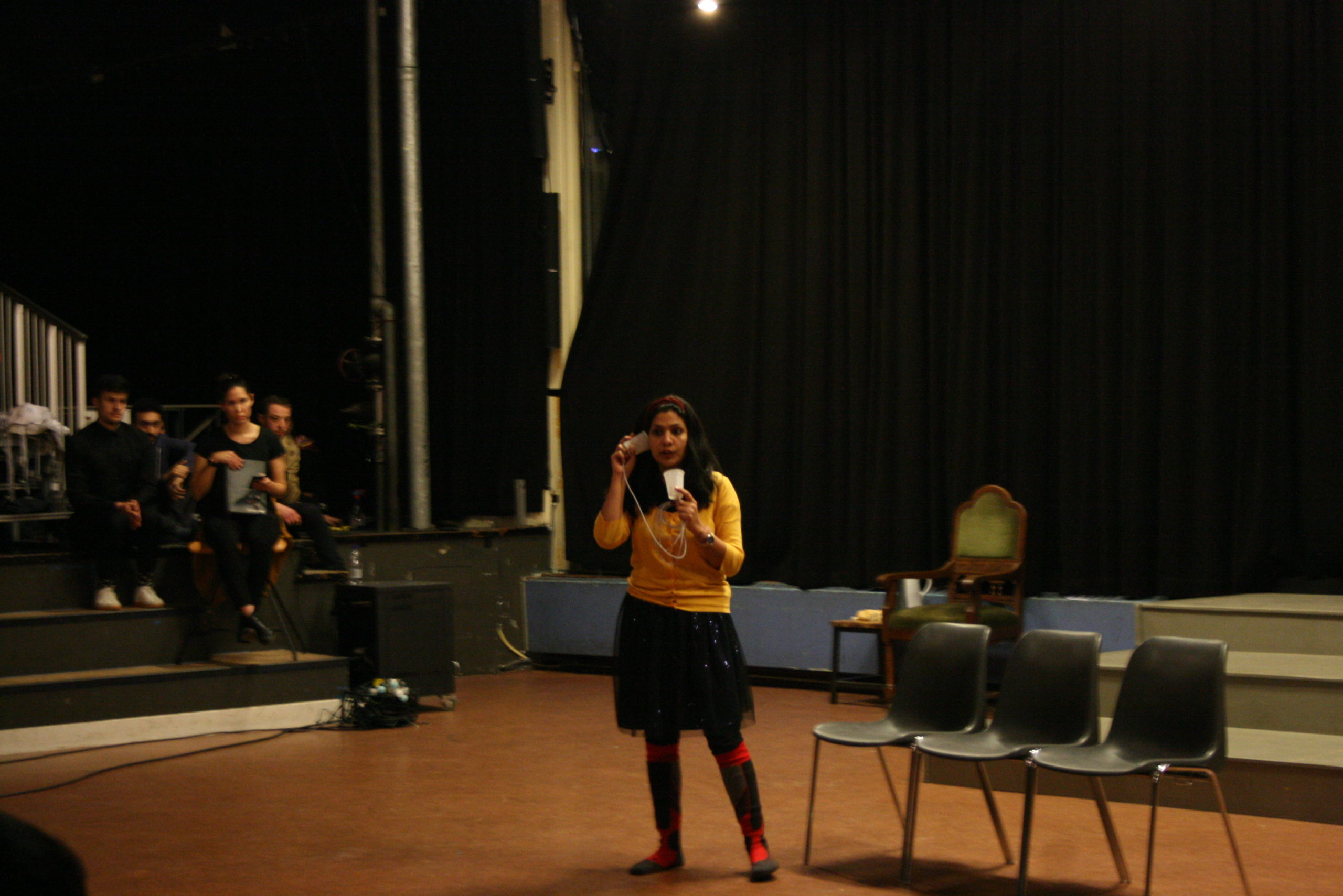 """Photo from the show """"Skin of our Teeth"""". A female actor on stage with a yellow cardigan holding a cup in front of her like it's a phone"""