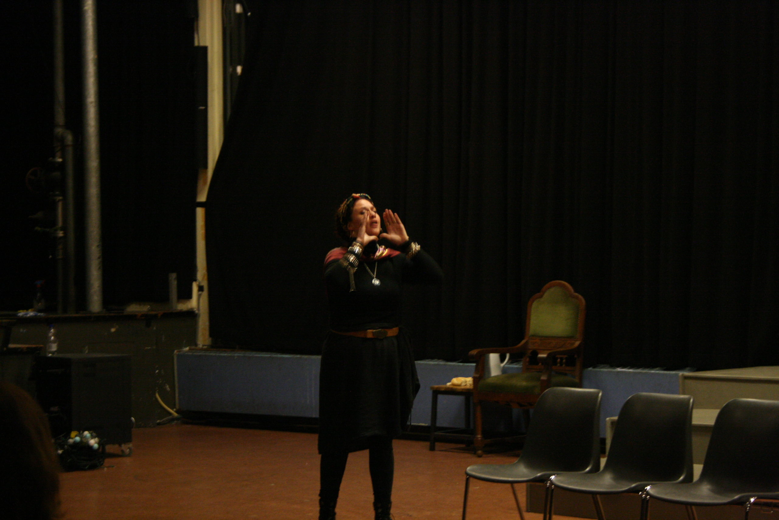 """Photo from the show """"Skin of our Teeth"""". A female actor on stage, dressed mostly in black, has her hands in front of her mouth like she's calling someone"""