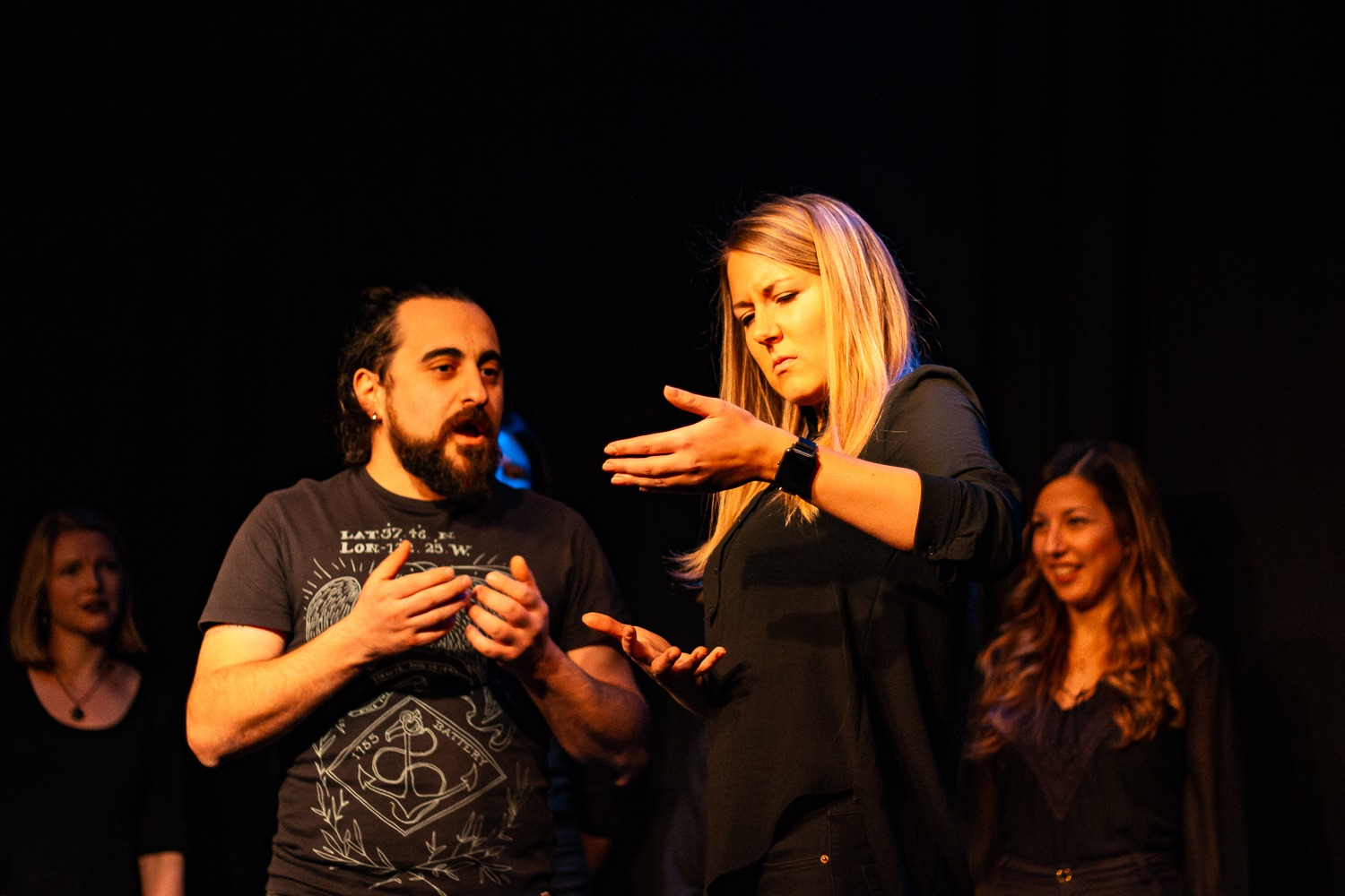 Act Attack's improv and physical show. A group of people on stage wearing black clothes. A man with beard speaks to a blonde woman who pretends to hold something in her arms.