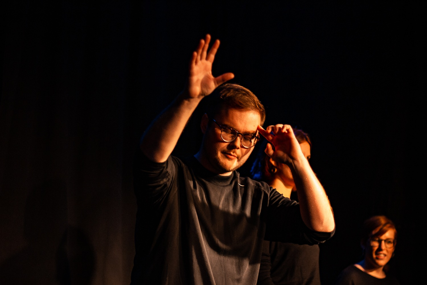 Act Attack's improv and physical show. A group of people on stage wearing black. A white man with glasses touches his forehead with his hand while reaching out his other hand. Eyes closed.