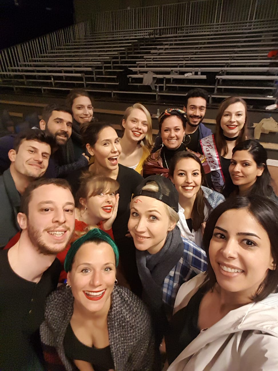 """Photo from the show """"Skin of our Teeth"""". Fifteen people take a group selfie in front of the stands"""