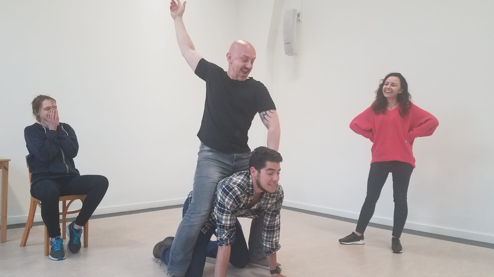 Acting Class Act Attack. Four people. One woman stands on the right, another sits on a chair, on the left, both laughing. Two men in the middle. One is on all fours, and the other one rides him, like a horse.