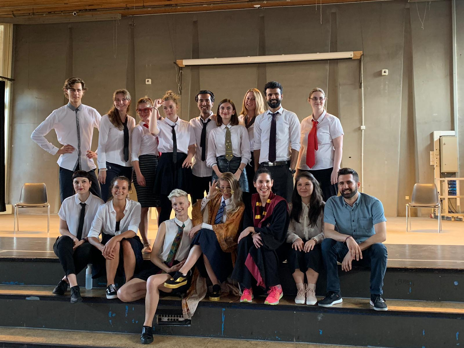 """From the rehearsal of the show """"the magic school"""". A group of people pose for the picture. Most of them wear a white shirt and tie"""