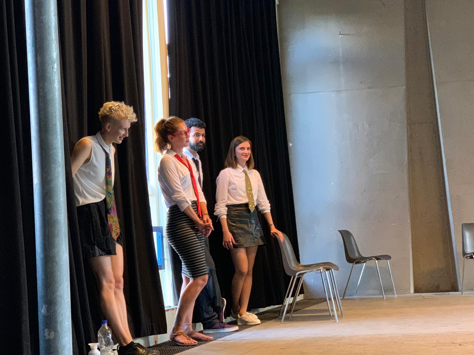 """From the show """"the magic school"""". Four actors stand next to the stage, wearing a white shirt and tie, with their back against a window, hidden by a black curtain"""
