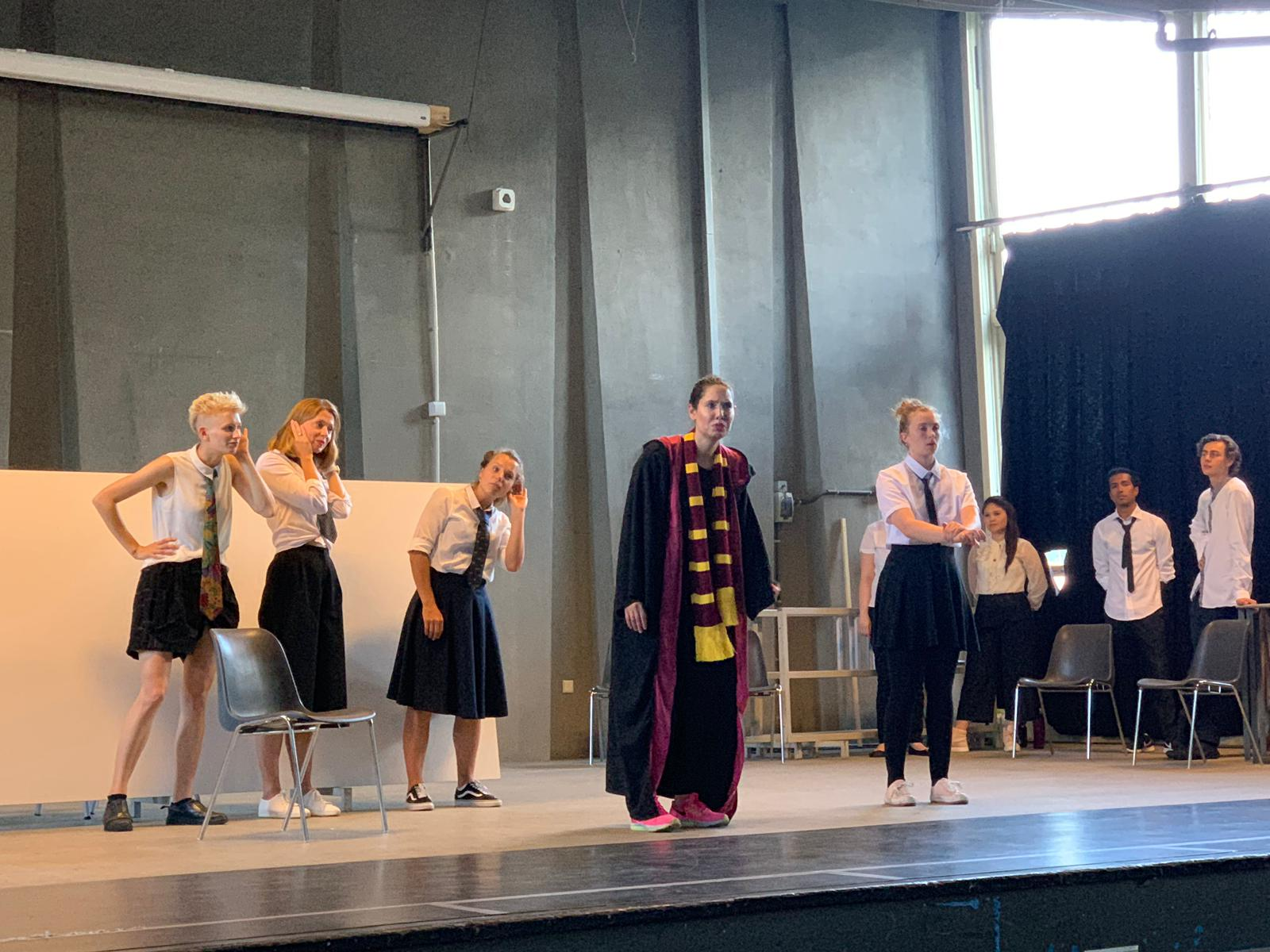 """From the show """"the magic school"""". Five actors on stage, four of them wear a white suit and tie. The fifth wears a cape and scarf, she is probably the teacher. Everybody faces the audience"""