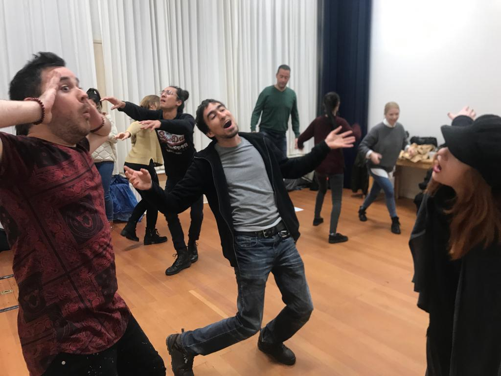 Act Attack's Improv and physical acting class. Two men are singing or they look shocked, while everyone else from the rest of the group does something different