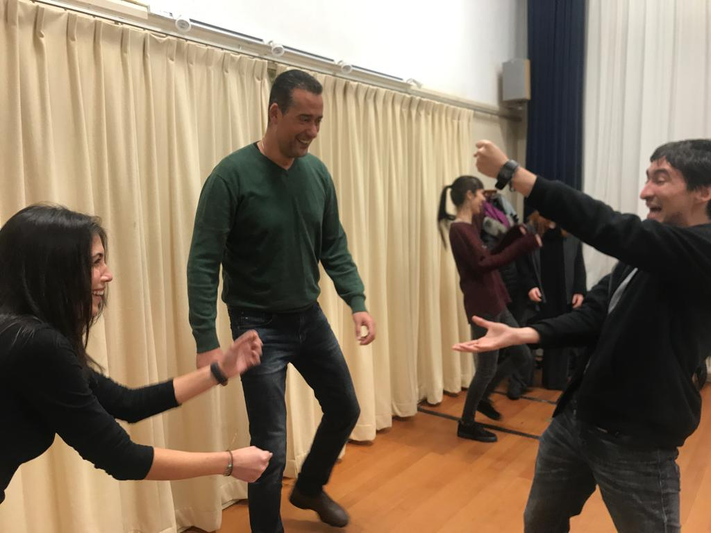 Act Attack's Improv class. Three people are standing.A man and a woman move their arms laughing. The third man looks at them.