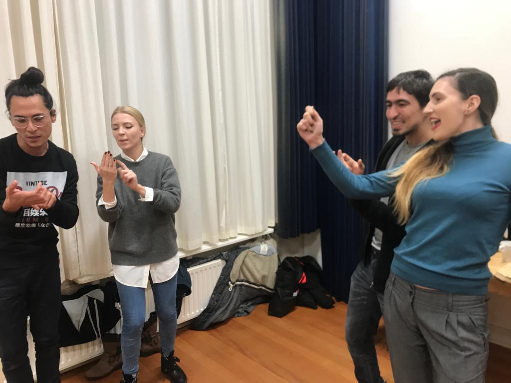 Act Attack's Improv class. A guy and a girl pretend to read, while a guy and a girl are watching them, cheering for them