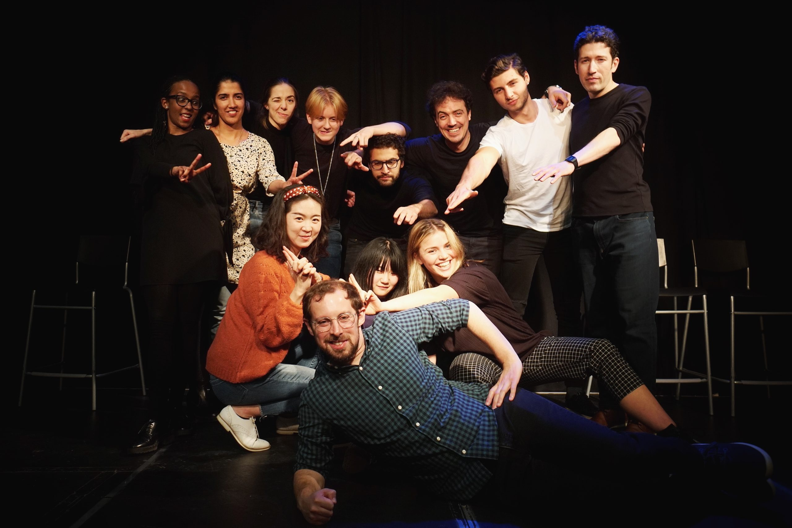 Act Attack's Pure improv show with Isaac, the teacher. Isaac is laying on the ground, the students are behind him, pointing at him