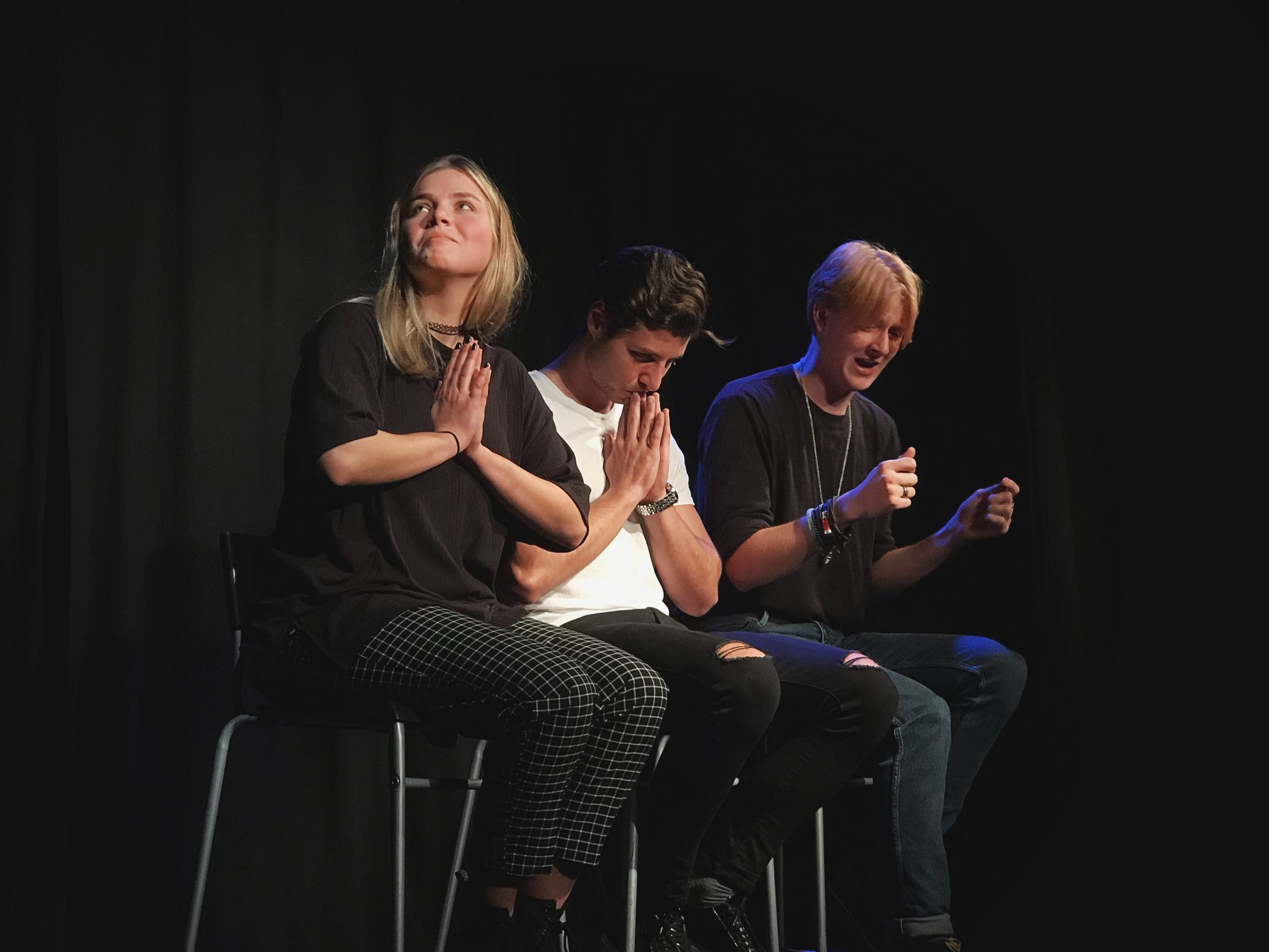 Act Attack's Pure Improv show. Two guys and a girl sit on bar stools. One of them pretends to drive, the other two have their palms facing each other in front of their chest