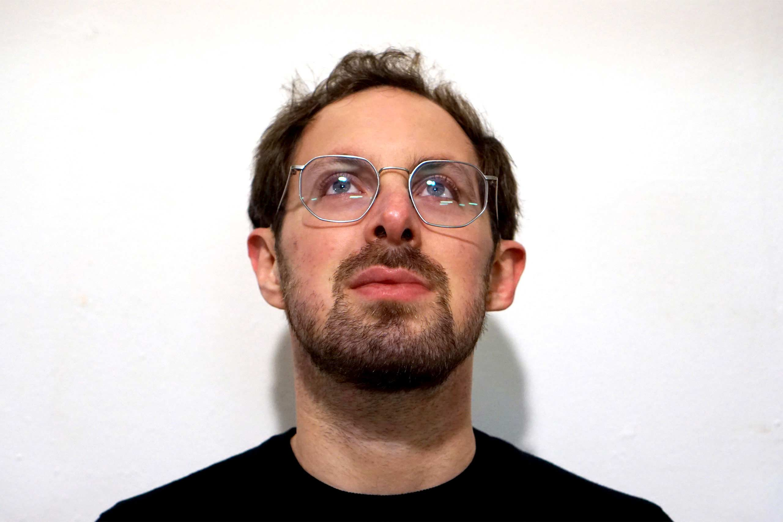 Act Attack teacher Isaac Lester Simon. Man, white, brown hair, blue eyes, beard, black top, grey metal glasses. He's looking up.