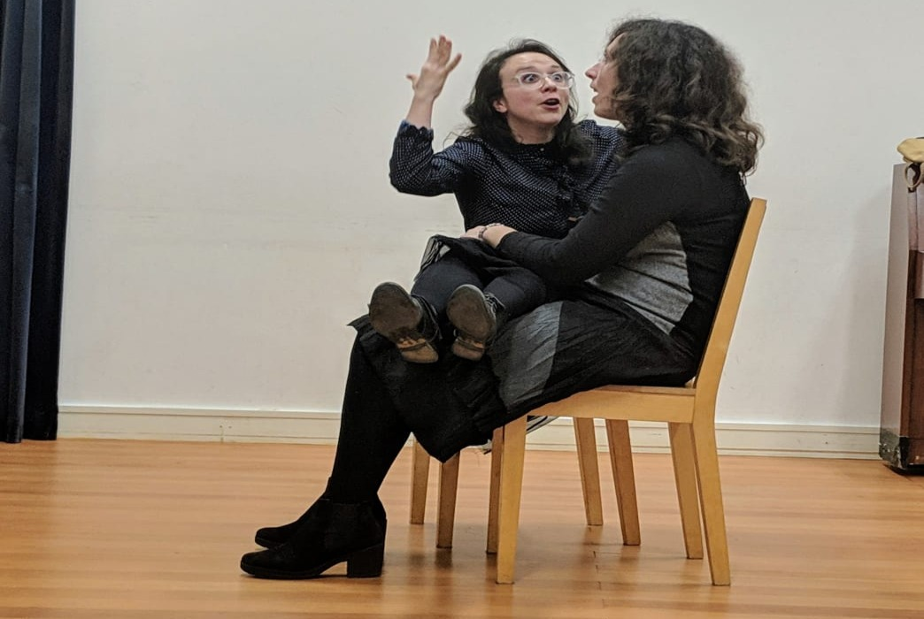 Two Act Attack's students are practicing. They are both women with brown long hairs. They sit on two chairs. One looks straight, the second one looks at the first one. She has a look of surprise, her hand is up in the air. And her legs are on the other woman's laps.